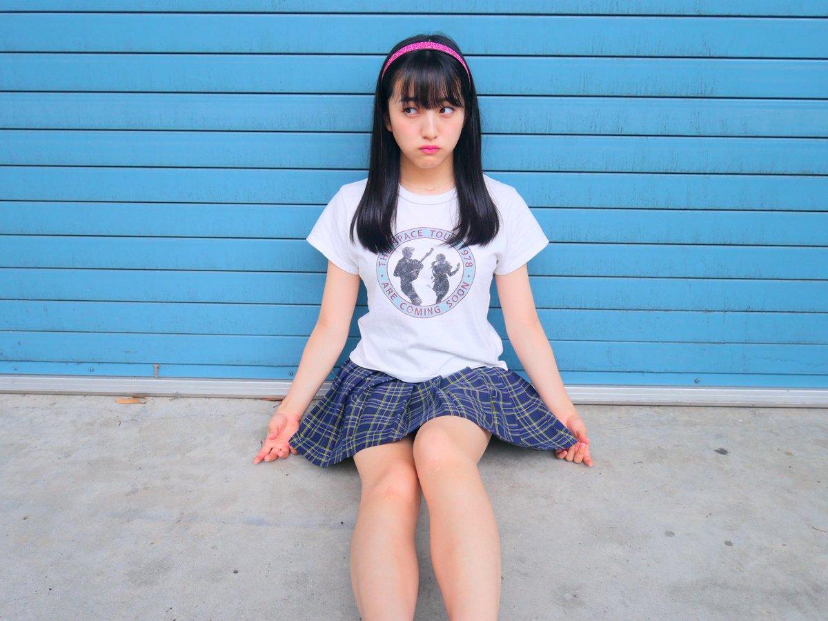 水色のシャッターの前で座り、視線を横へ外すHKT48の田島芽瑠