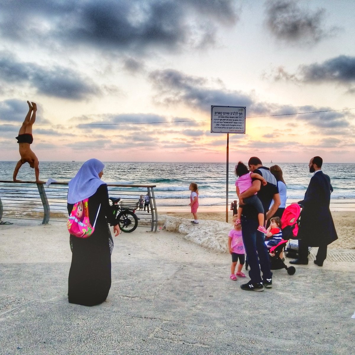 Only in #Israel Orthodox Jews along with Arabs watch half-naked man doing handstand during Tel Aviv sunset <br>http://pic.twitter.com/hY1lqrzyHs
