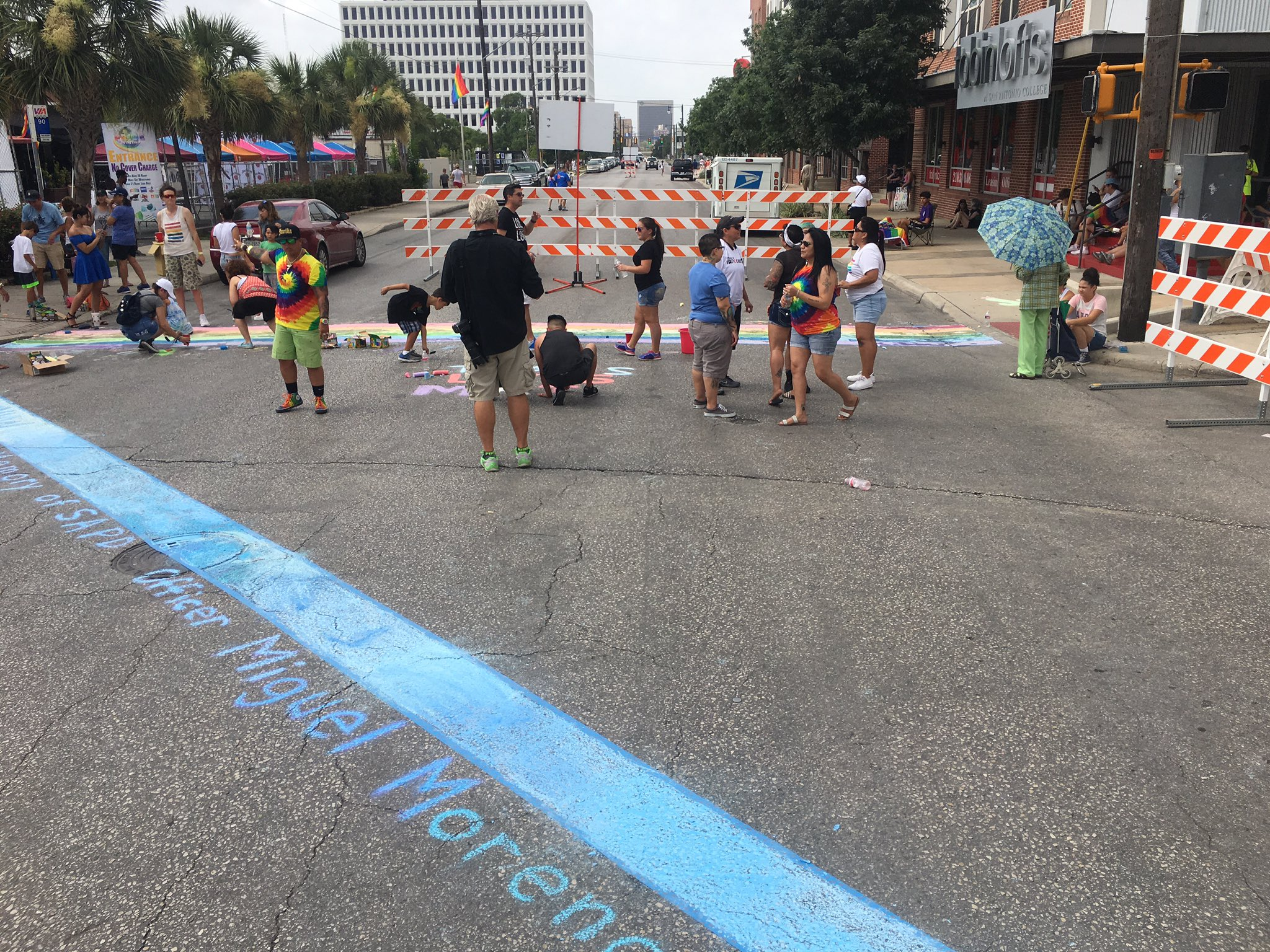 """""""In memory of SAPD officer Miguel Moreno #1603"""" is added to thin blue line as chalk rainbow crosswalks are painted at Evergreen and Main. https://t.co/O4z0bKwuw3"""