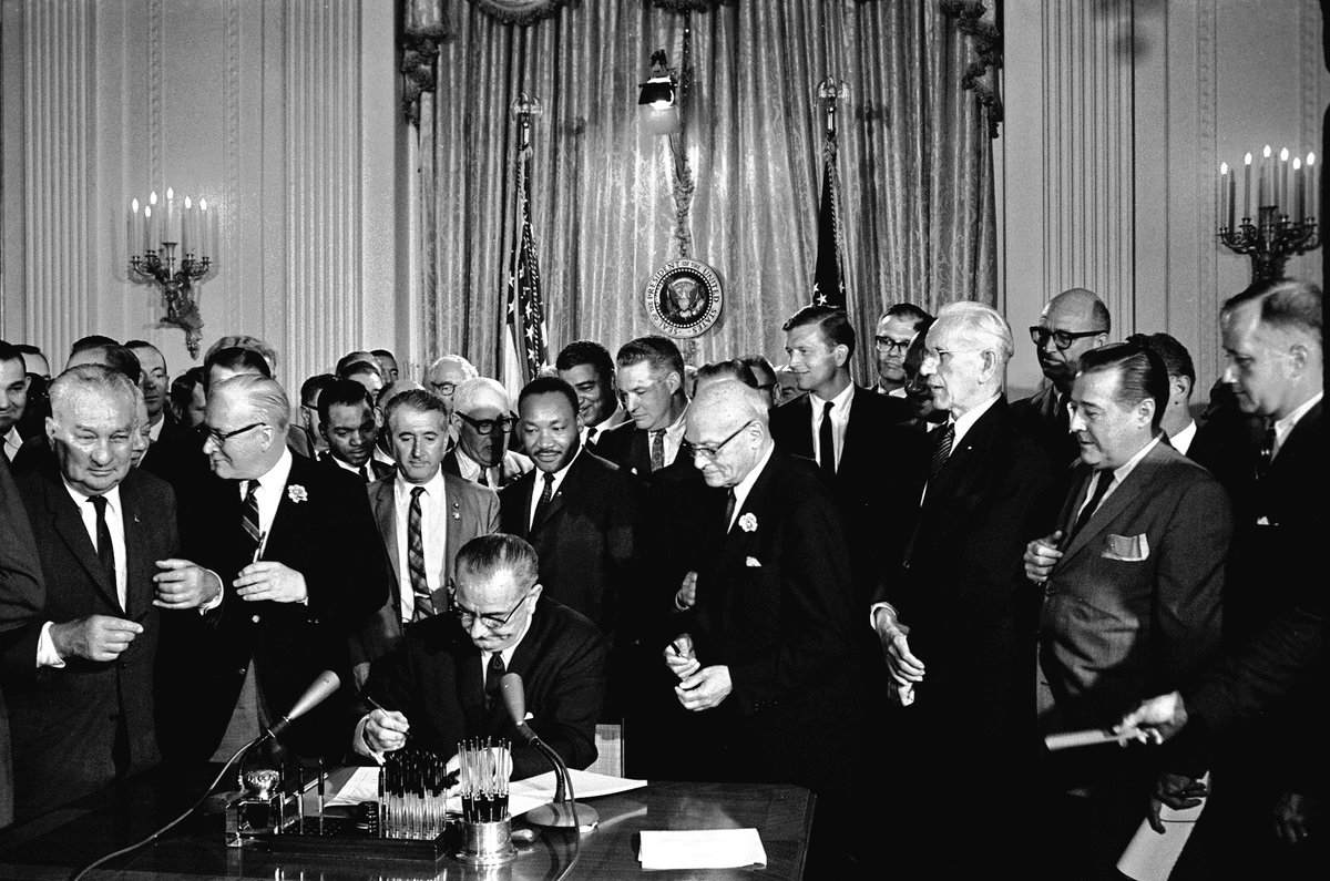 #OTD in 1964, President Lyndon B. Johnson signs the 1964 Civil Rights Act as Martin Luther King, Jr., and others, look on. #APeoplesJourney