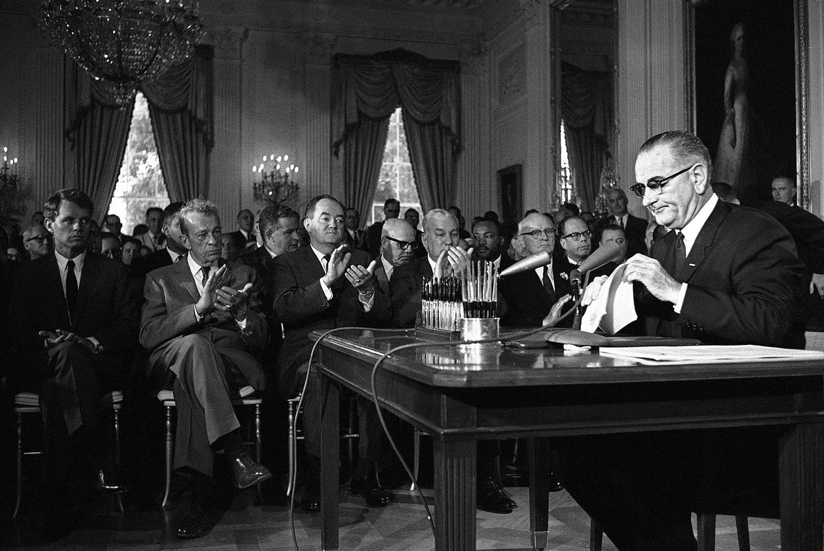 LBJ signs Civil Rights Act in White House East Room, today 1964:   #LBJL