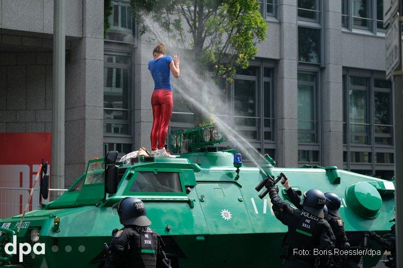 Eine Frau klettert während der Proteste gegen den #G20-Gipfel in Hamburg auf einen Polizeiwagen und wird mit Pfefferspray besprüht. (sbr)