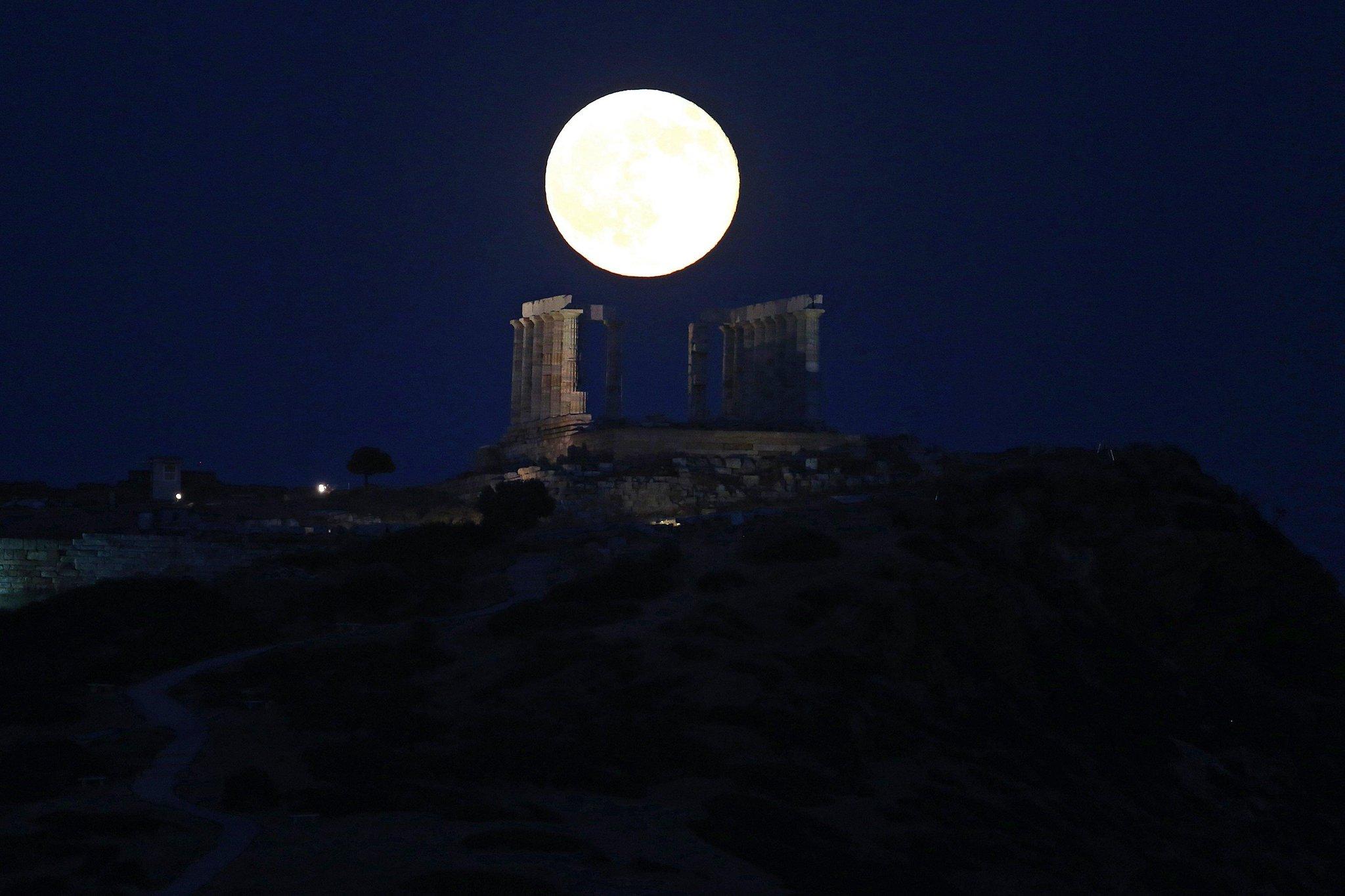 La luna llena se levanta sobre el antiguo templo de Poseidón, en el cabo Sounio, Grecia