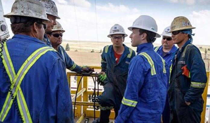 Mark Zuckerberg with oil workers and his coveralls backward