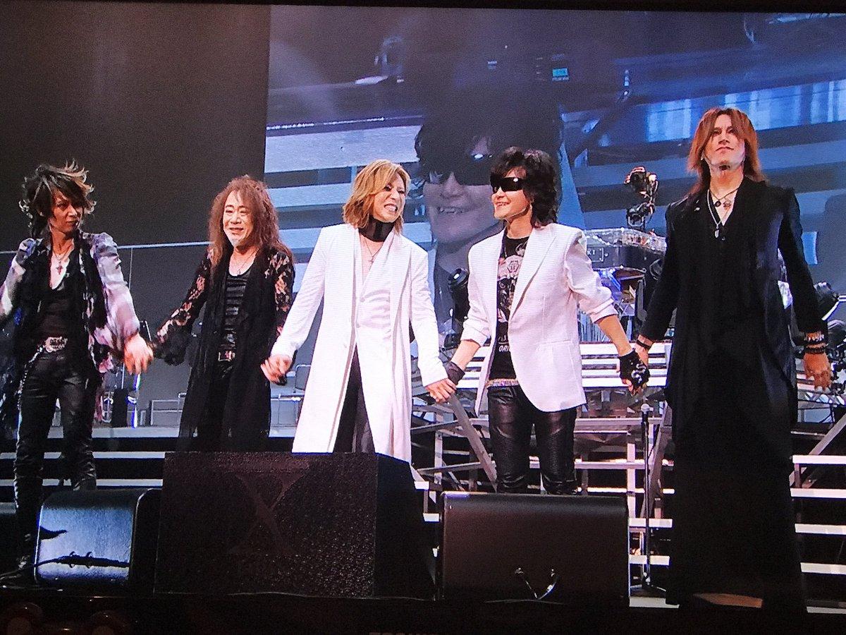 ステージ上で手をつないで並んでいるメンバー5人のX JAPANの画像