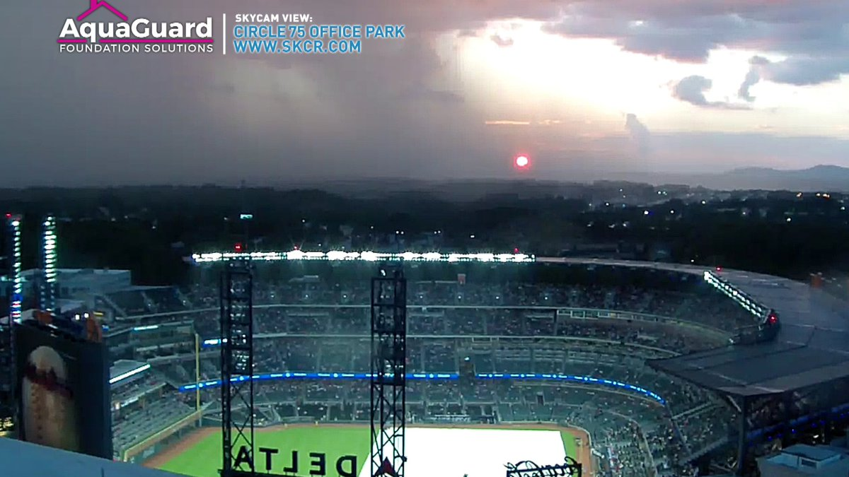 Tarp on the field, 1 lone shower over #SunTrustPark and nice sunset in the background. #IsolatedShowers #11Alive
