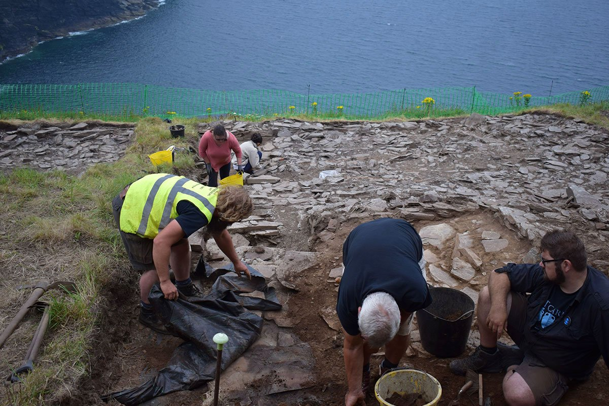 Here (under the tarpaulin) you can see the slate floor of an early medieval building, with a flight of steps in the background. #TintagelDig https://t.co/lOguQNkTda