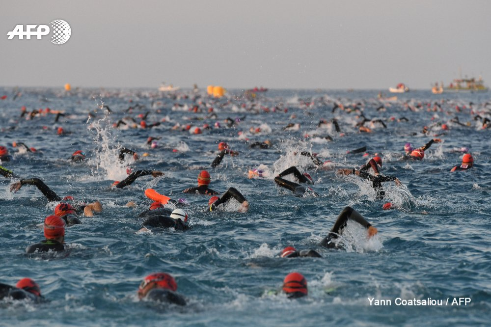 Participants kick off the swimming race of the 13th Ironman thriathlon in Nice
