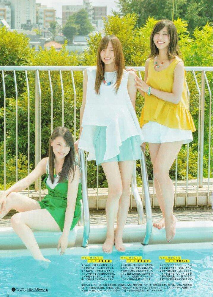 メンバーとプールサイドに立っている白いシャツを着た梅澤美波の画像