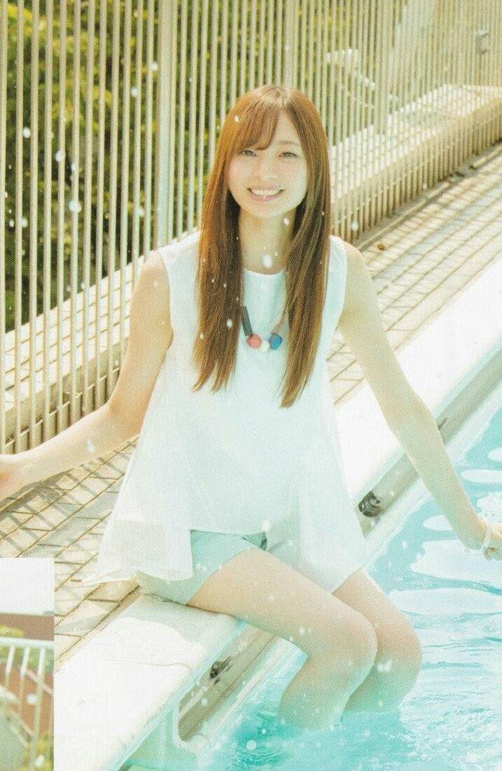 プールサイドに座ってプールに足を入れている梅澤美波の画像