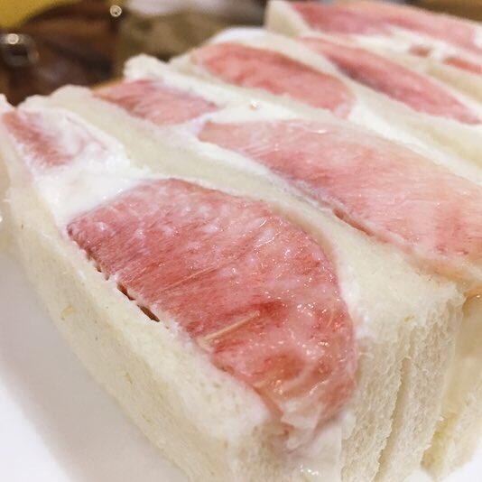 とにかくフルーツサンドが好きだ。一番好きなのは京都のヤオイソ。スポンジじゃだめ。きめの細かい真っ白なパンが上顎に触れるときの冷たさ。噛みしめれば記憶の中のミルクの味のするクリームがフルーツの爆発する香気を伴って口の中に広がる。今まさにやっているであろう桃のサンドが食べたいなぁ。 pic.twitter.com/hUaX05VgzM