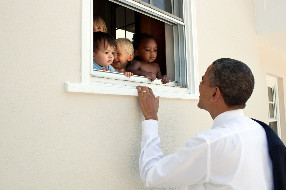 Obama looking up at an open window with babies of various ethnic backgrounds looking out
