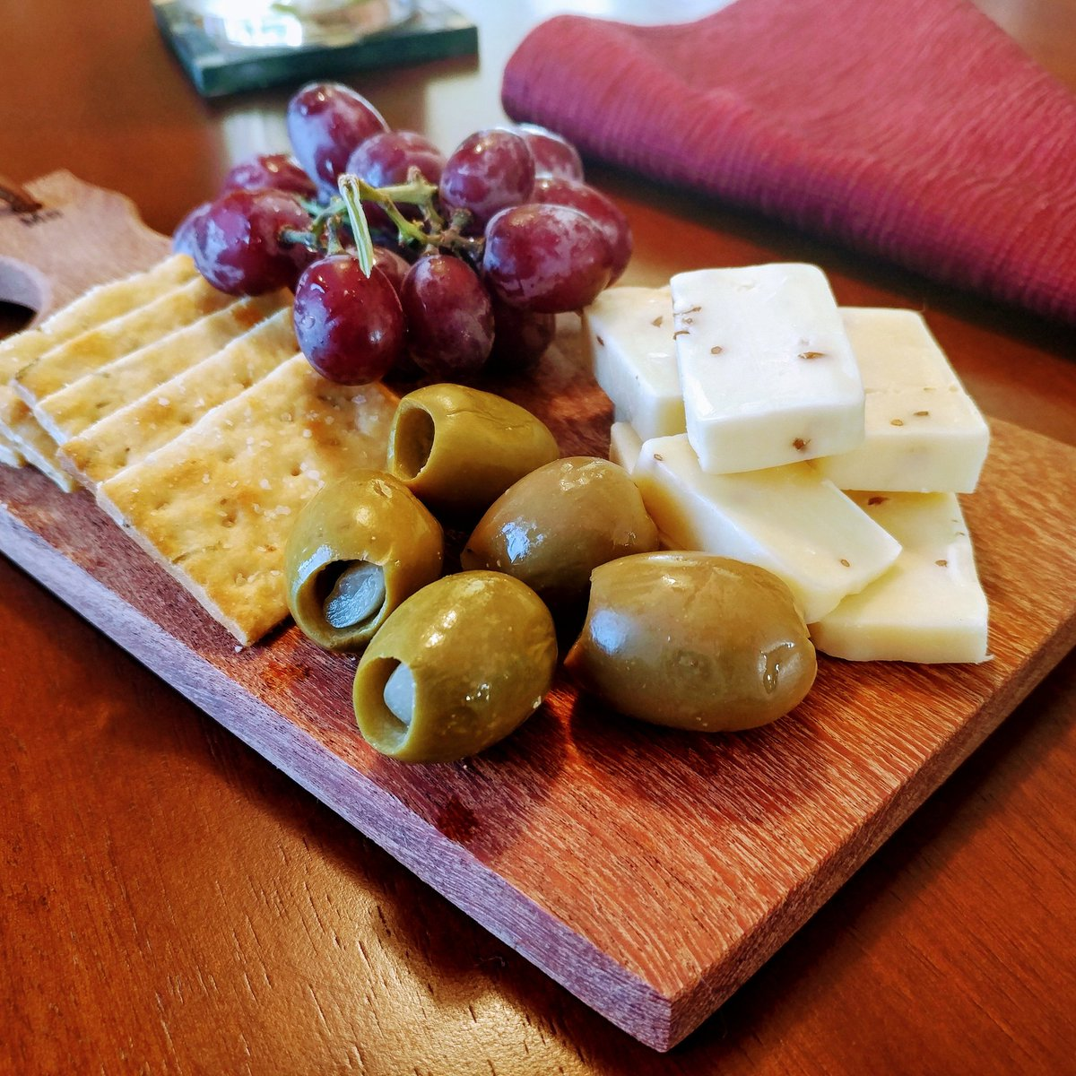 An itty-bitty cheese board w/ crackers, garlic stuffed olives &amp; red grapes.  #FoxyCuisine #cheeseboard #crackers #cheese #olives #grapes<br>http://pic.twitter.com/NMPuGBAVhf