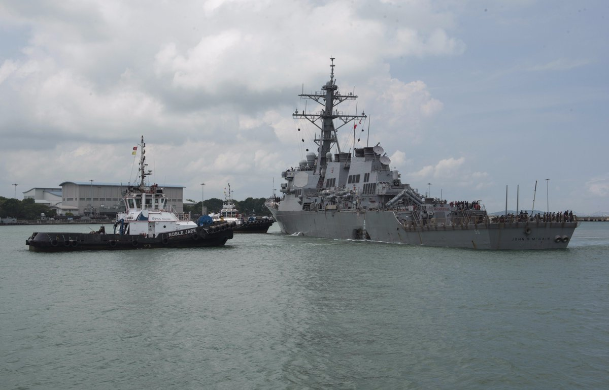 Navy releases shots of the USS John McCain as it arrives in Singapore. Big hole.