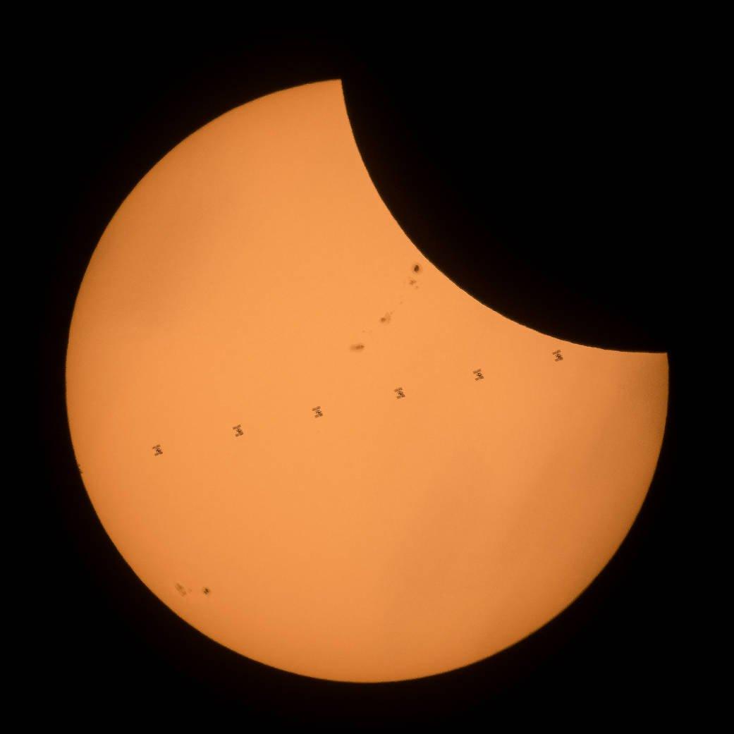 日食中の太陽面をISSが通過