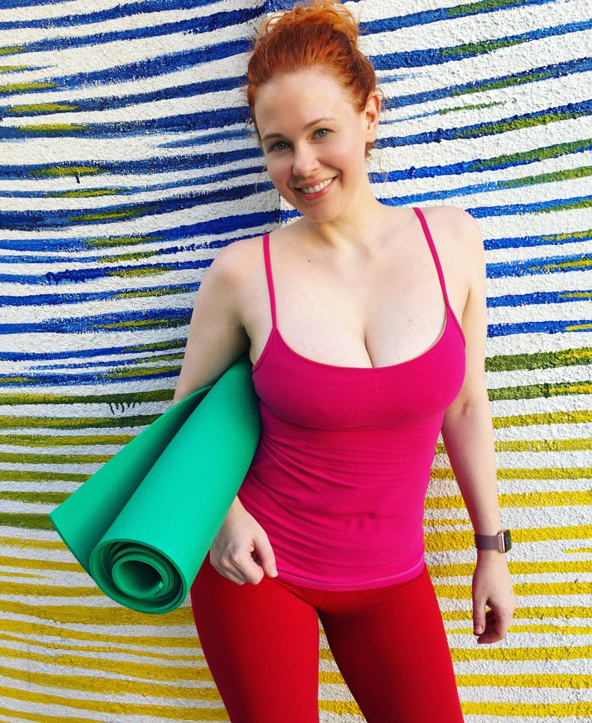 Maitland ward poses with her yoga mat