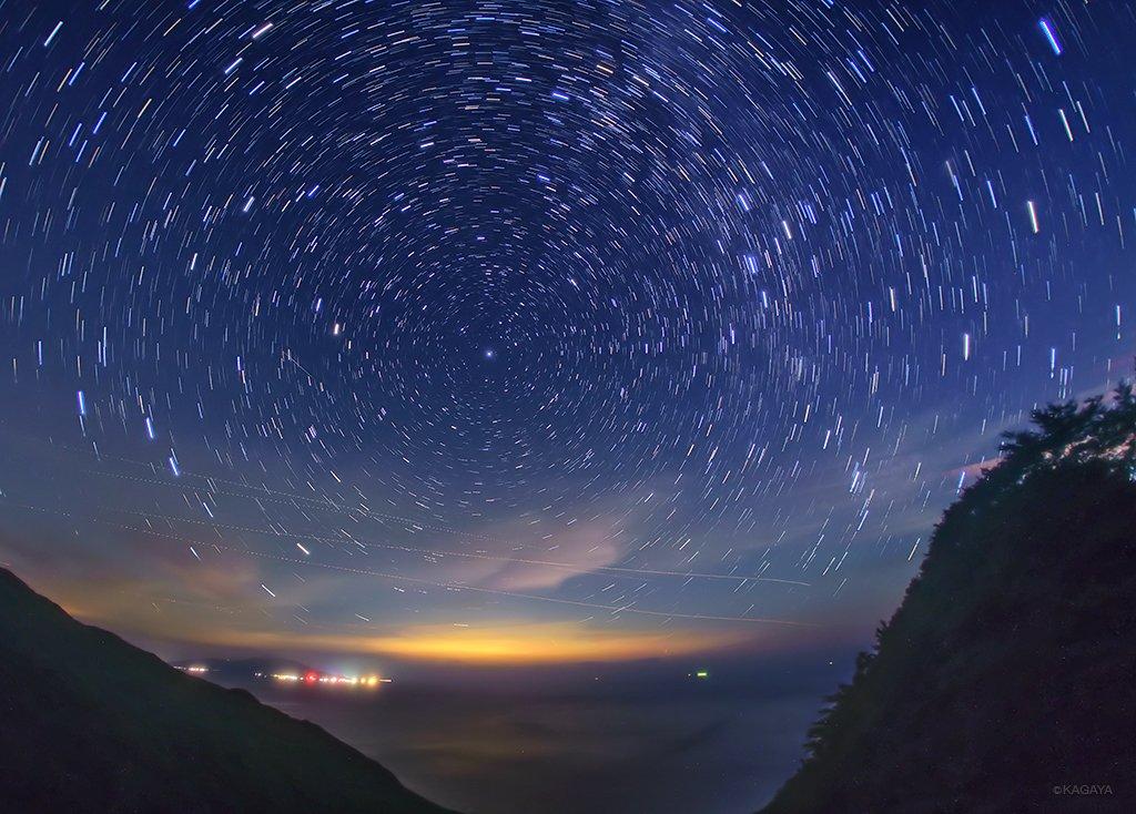 めぐる北天の星々。円弧の中心が北極星。左下に北斗七星、右上にカシオペア。左下の灯りは三宅島、水平線上のオレンジの光は東京方面の明かりです。(先日御蔵島にて撮影)今週も穏やかな一週間になりますように。 pic.twitter.com/ZMxXlPNZO9