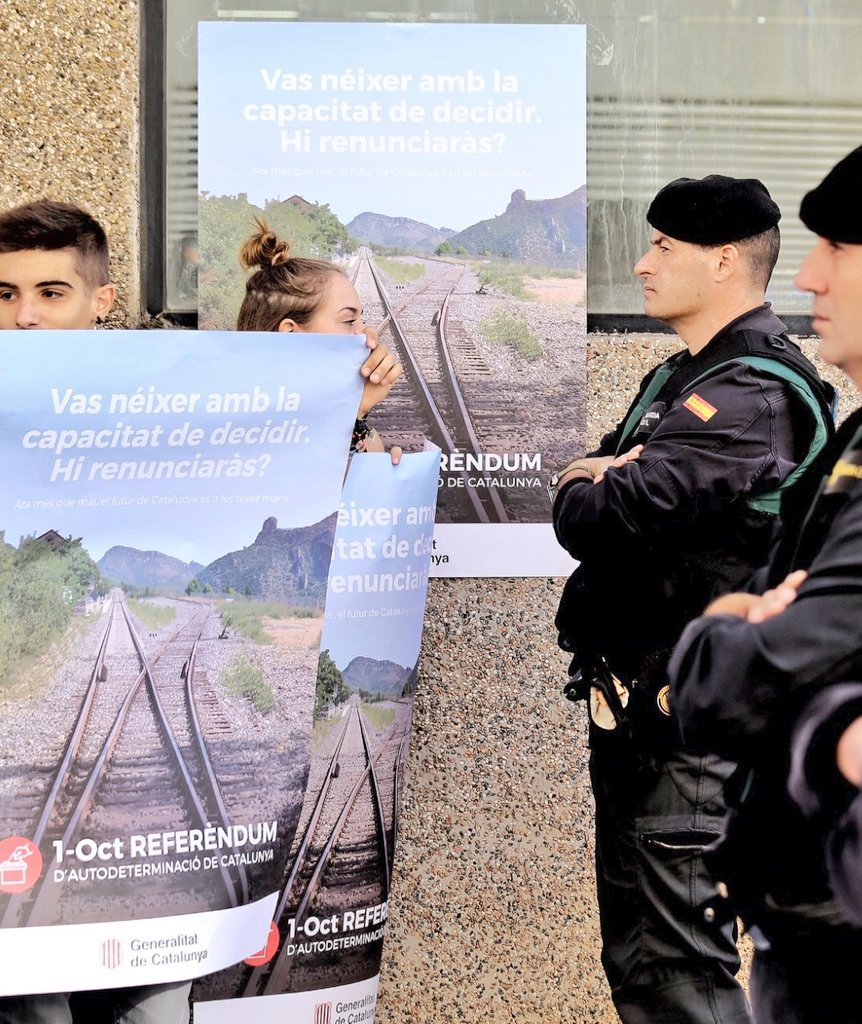 Protesters with posters of #Catalonia&#39;s #independence #referendum face Spanish military police in search of mail #indyref docs in #Terrassa <br>http://pic.twitter.com/4AEjOKeadM
