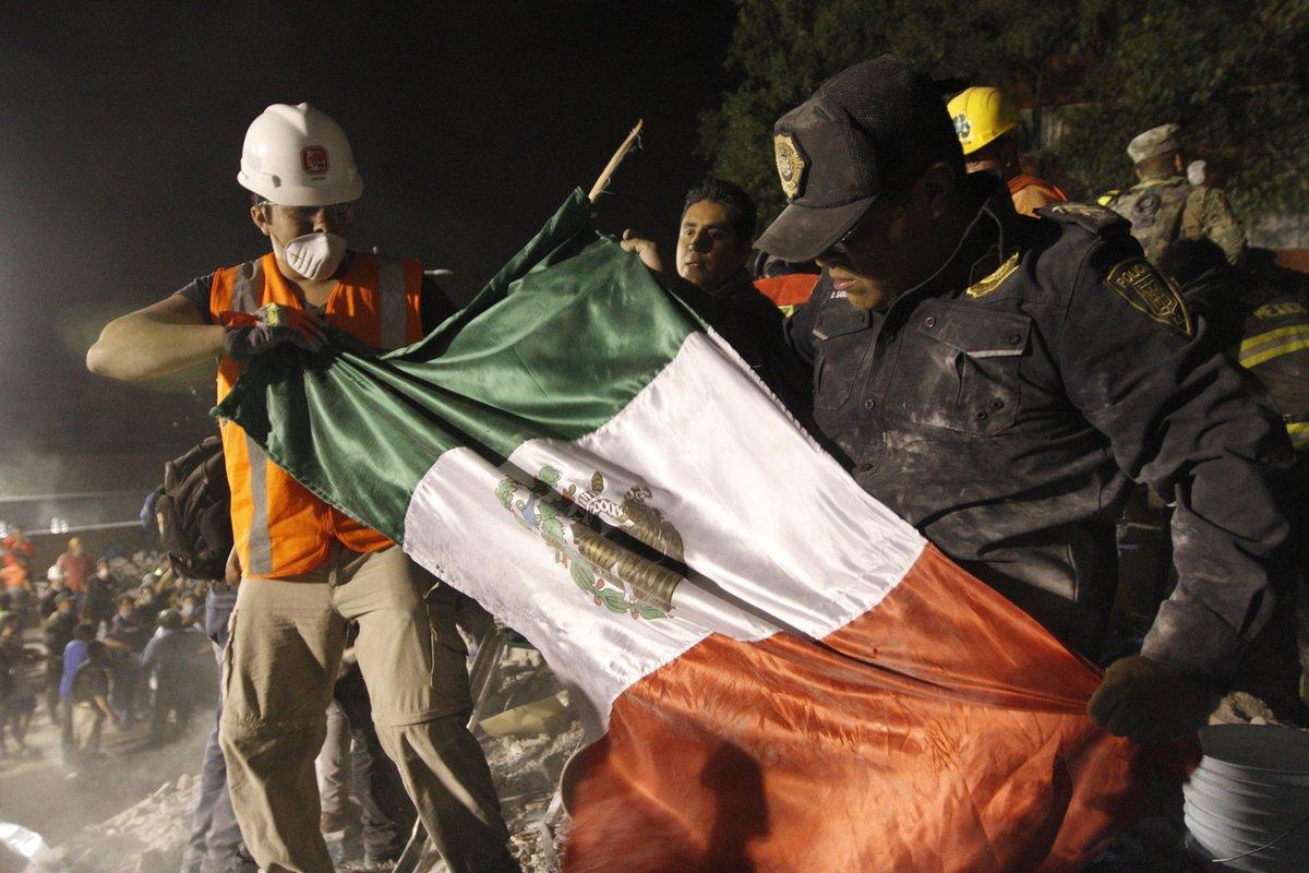 Extienden bandera de México entre escombros en #CDMX #FuerzaMéxico (Foto: Notimex)