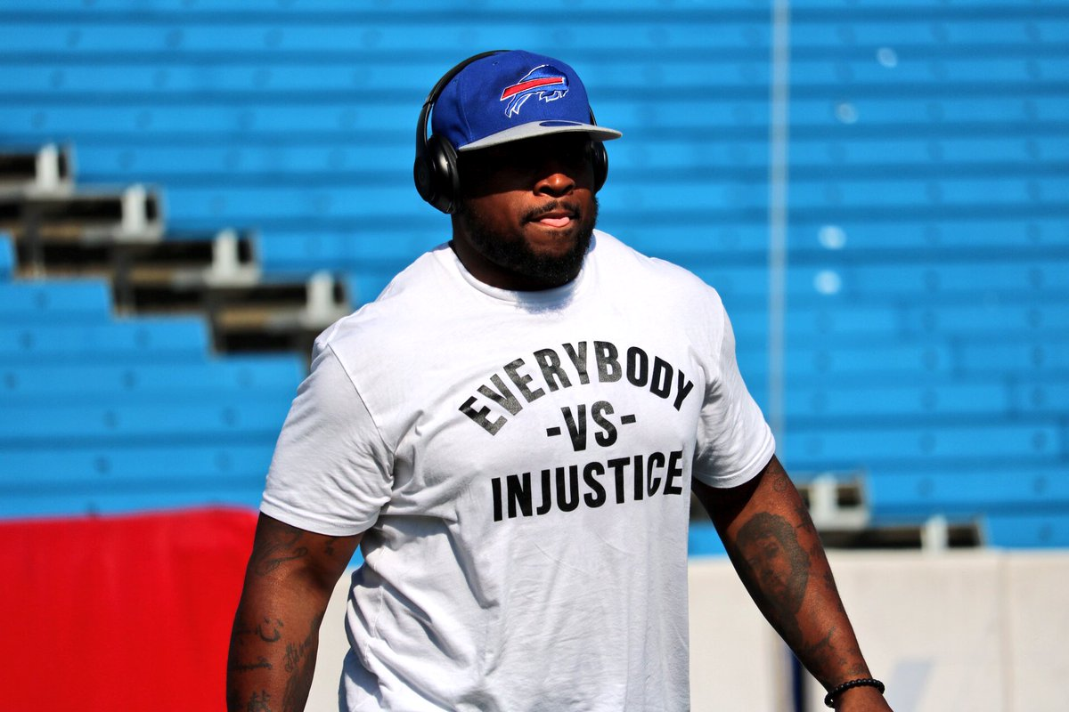 Mike Tolbert wearing a t-shirt that says 'everybody vs injustice' duri...