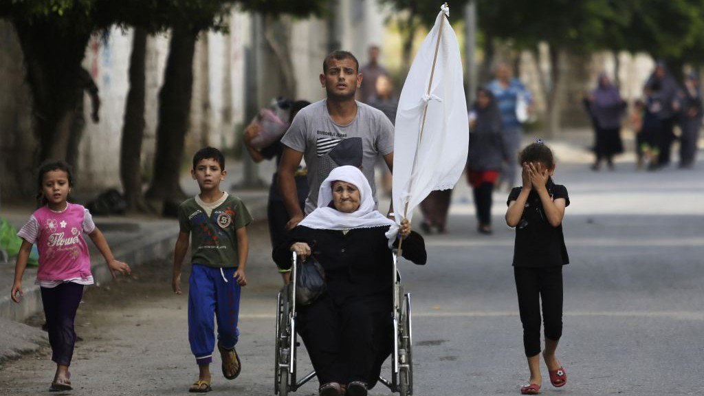 Somebody&#39;s #grandmother. #Disabled elderly woman in #wheelchair waving makeshift #whiteflag flees along with children from #Zionist #terror.<br>http://pic.twitter.com/4SIGgn4Nzd