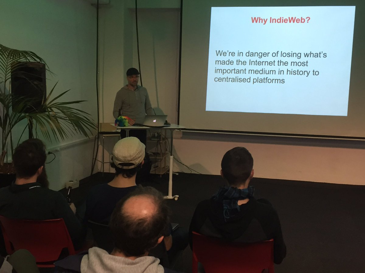 Photo of Timo Reitnauer presenting on the IndieWeb at the PHP Wellington Meetup with a slide titled 'Why IndieWeb?' and text 'We're in danger of losing what's made the Internet the most important medium in history to centralised platforms'