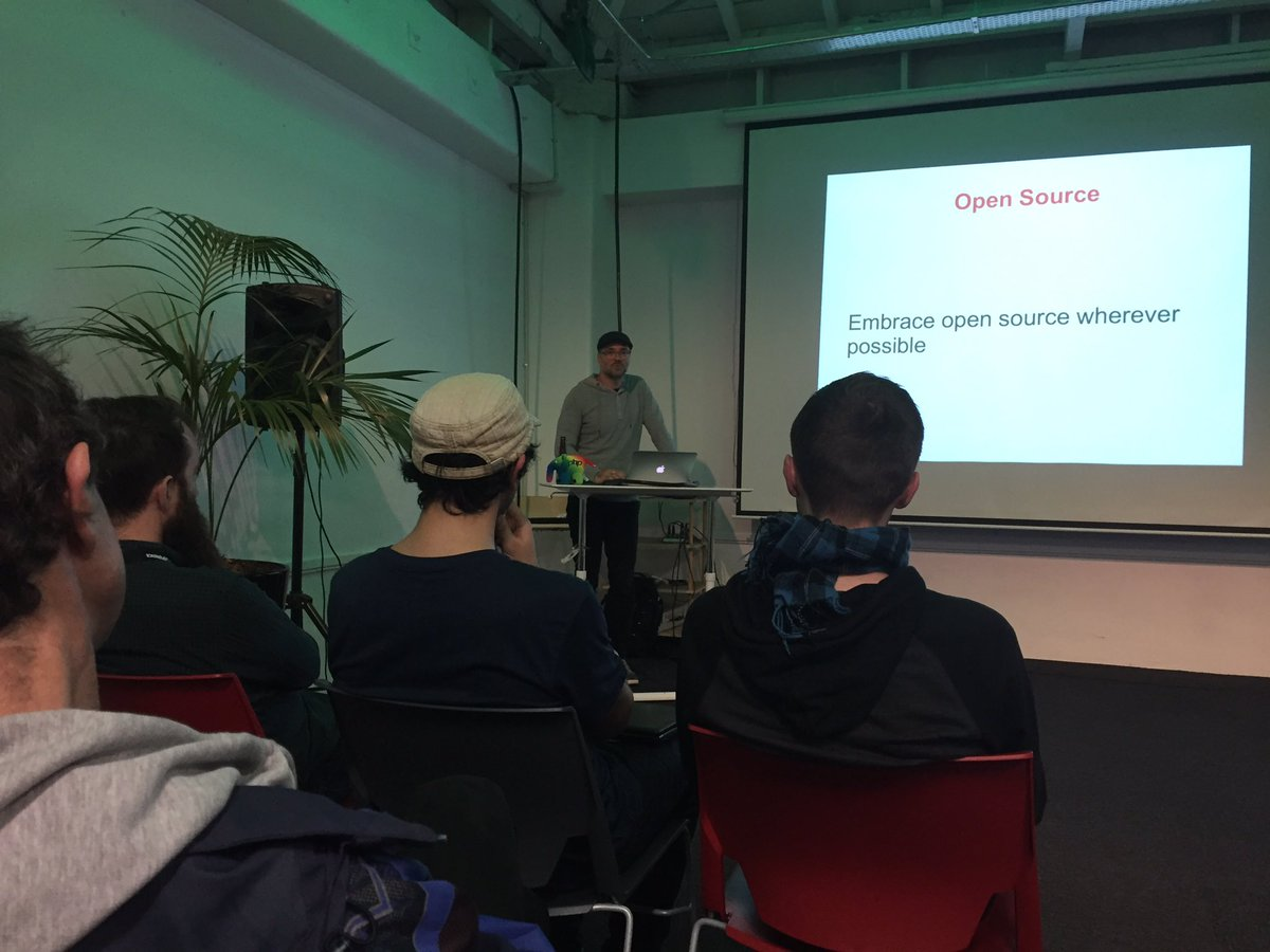 Photo of Timo Reitnauer presenting on the IndieWeb at the PHP Wellington Meetup with a slide titled 'Why IndieWeb?' and text 'Embrace open source wherever possible'