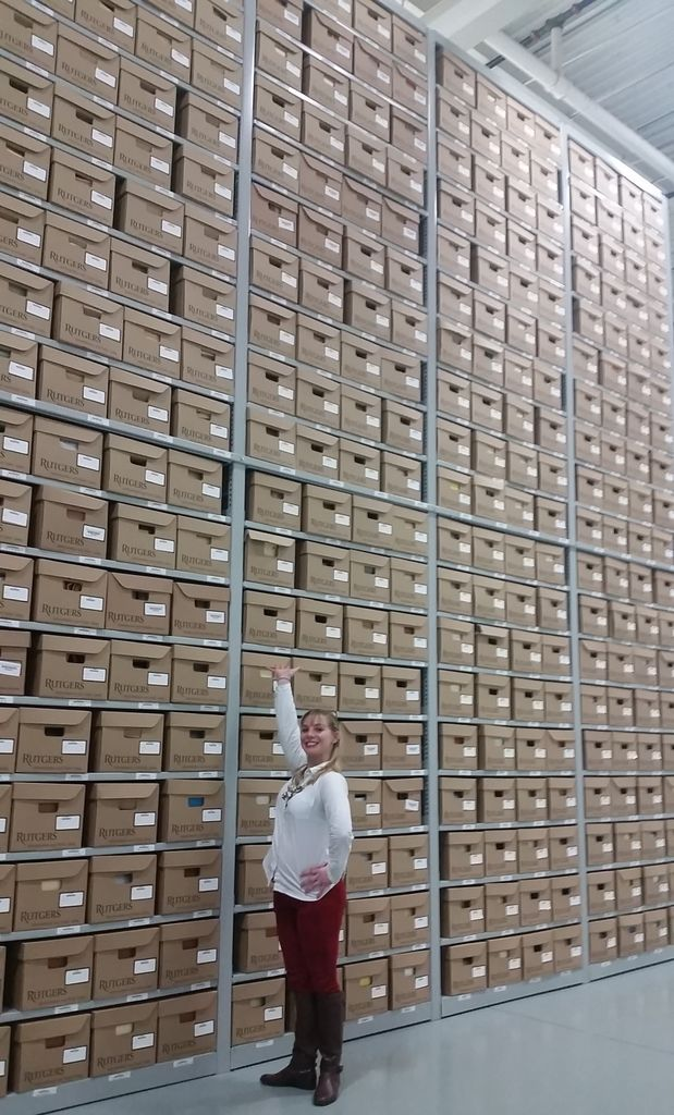 Archivist standing in front of a wall of boxes that is floor to ceiling.