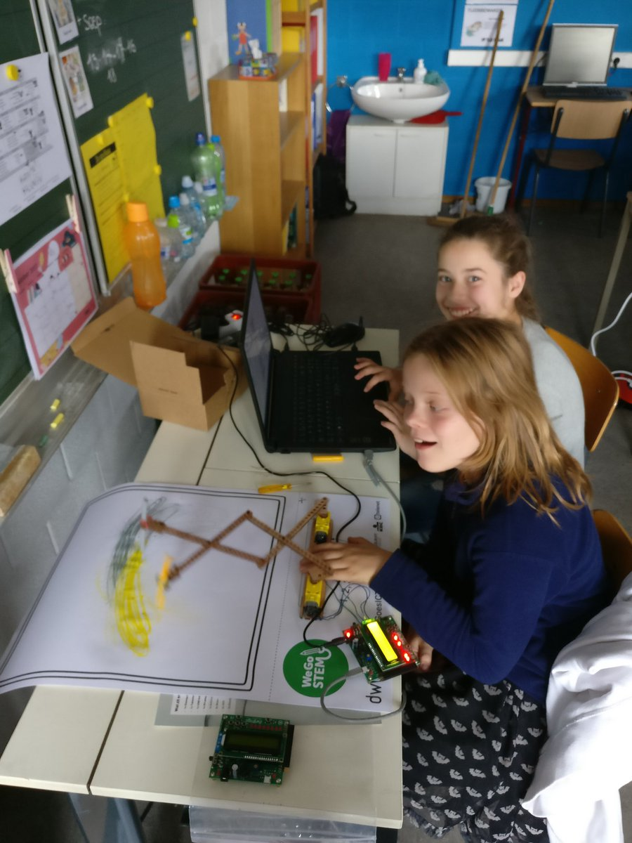 A robot in action. Note that these young ladies are dual-wielding two markers!