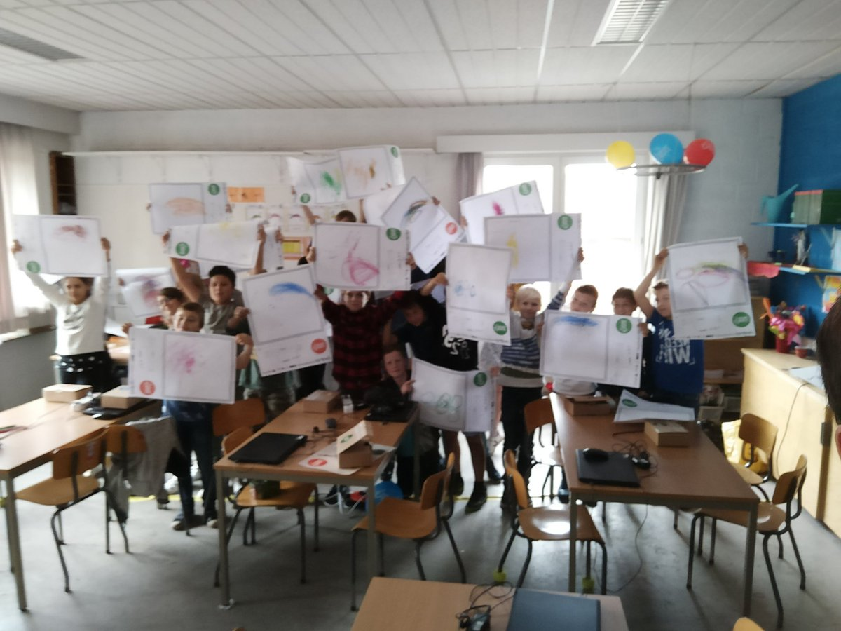 A class proudly showing their drawings.