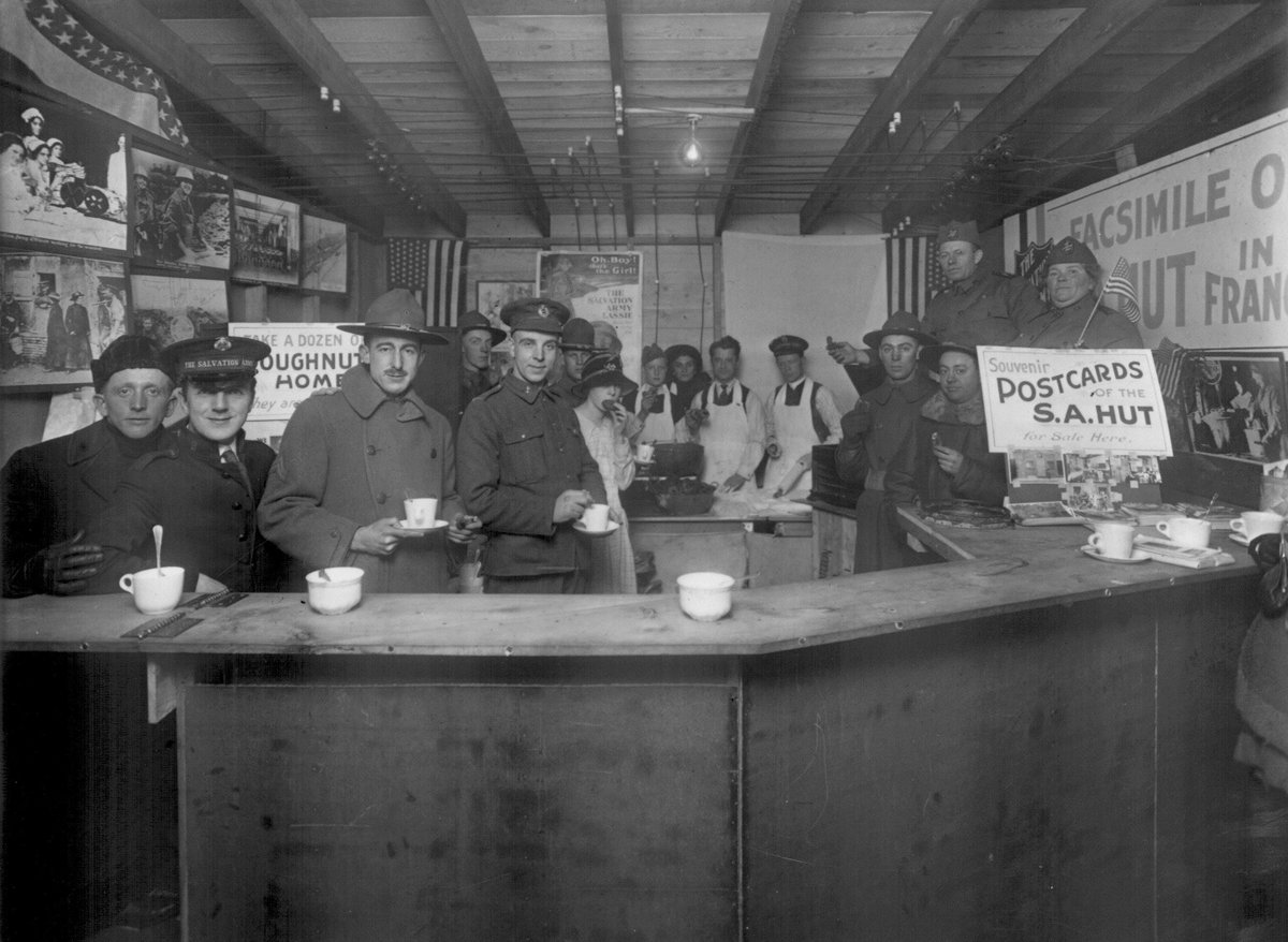 Allied soldiers and Salvation Army workers having doughnuts and coffee in a Salvation Army hut in France, 1918