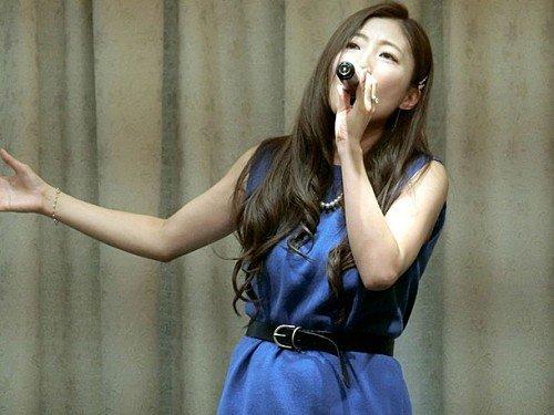 青いサテンのワンピース姿で歌う歌手活動中のティアラ