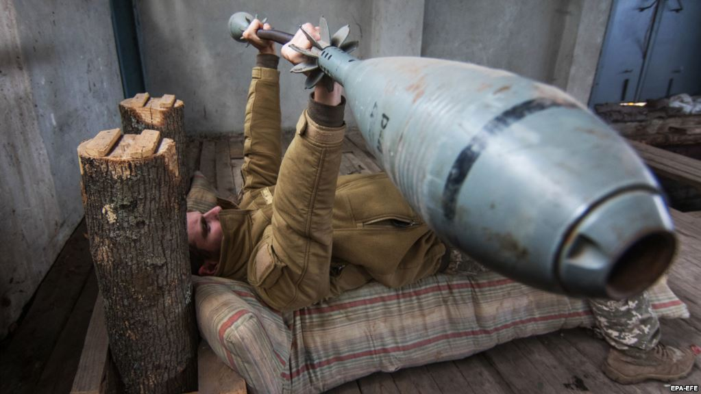 A Ukrainian serviceman exercises using a 35-kilogram barbell made from a 120mm mortar shell, not far from front line Vodyane village.