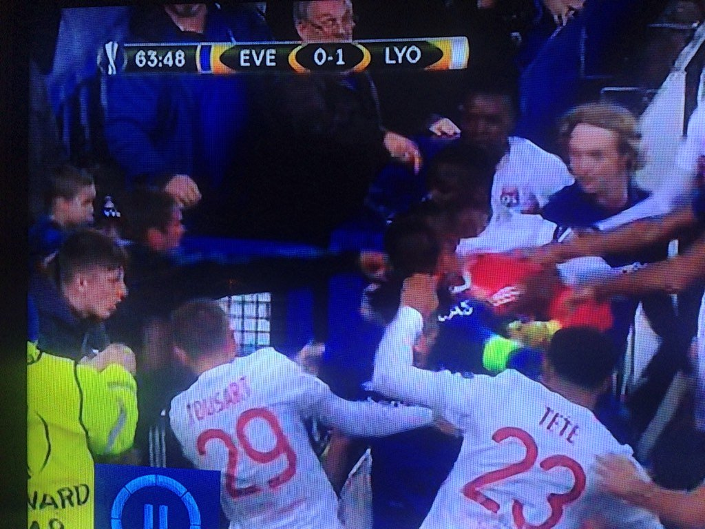 Who is this idiot on the left trying to punch a player, while HOLDING...