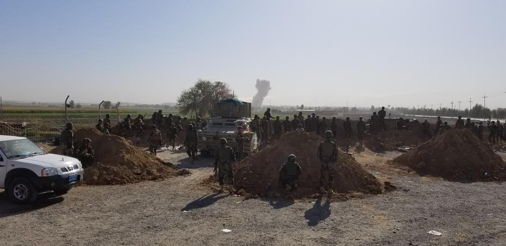 Kurdish troops cheer when they see an explosion among the Iraqi ranks