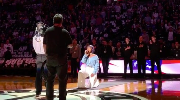 National anthem singer takes a knee whil...