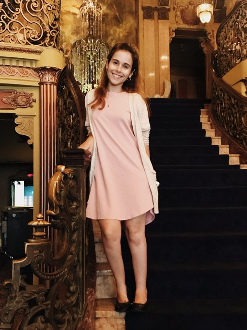 Andrea wearing a pink dress and a beige sweater. She's standing on a grand staircase smiling at the camera.