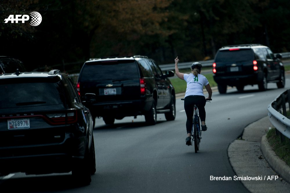 A woman on a bike gestures as the motorcade with US President Donald Trump departs Trump National Golf Course in Sterling, Virginia
