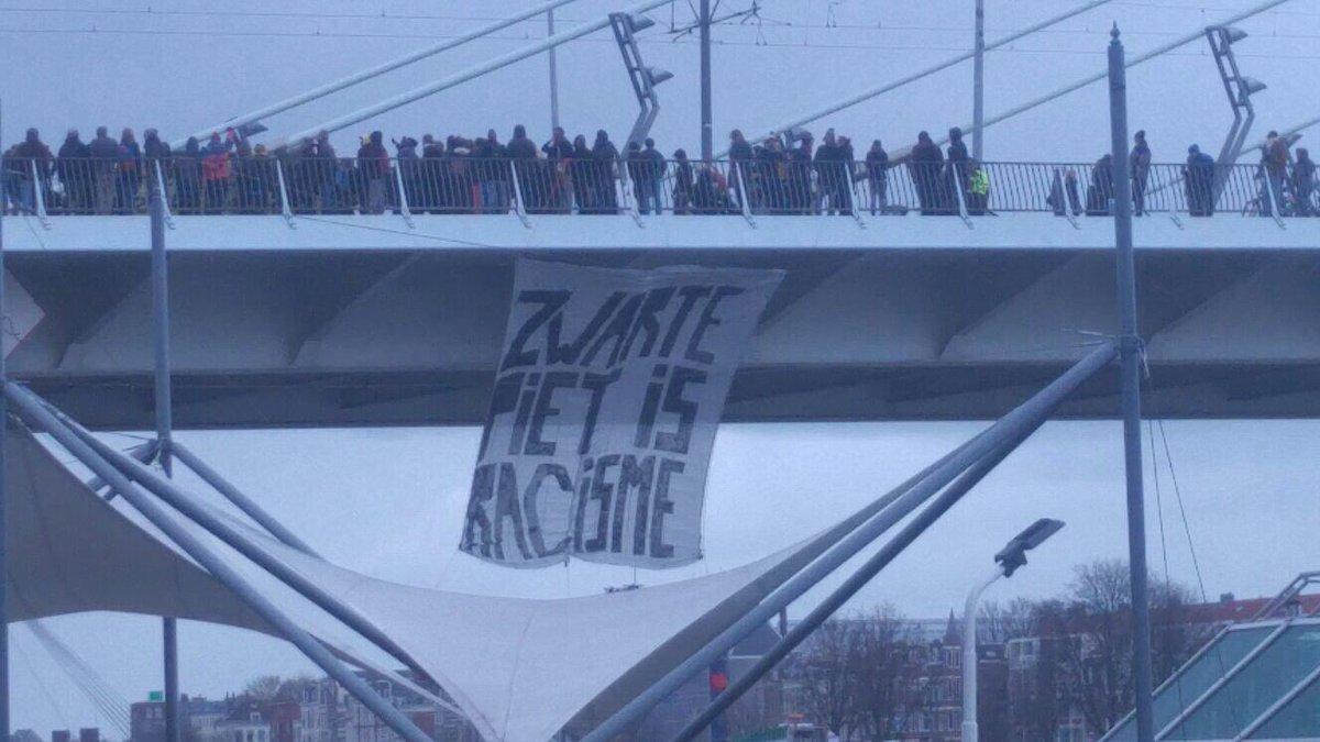 Netherlands: Movement against Zwarte Piet (racist caricature of the servant that helps the local Santa Klaus) blockades most important Dutch bridge in the day of its official arrival. Follow @stopracisme2017 #BlackLivesMatter  #StopRacisme #KickOutZwartePiet<br>http://pic.twitter.com/U1UCXzOB6w