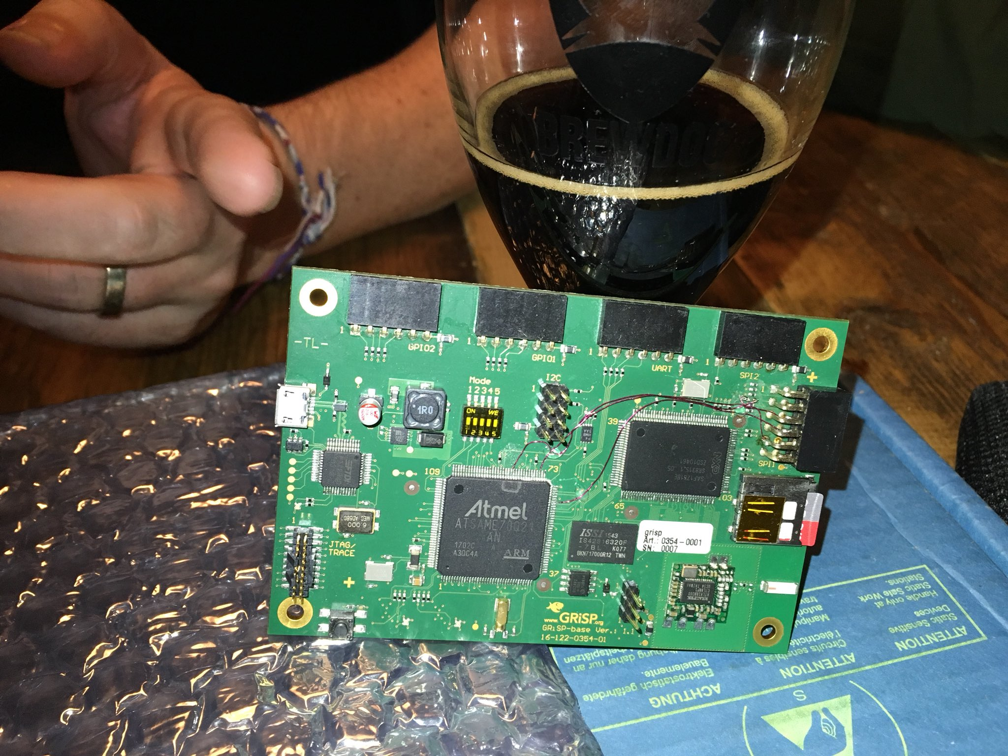 A GRiSP board, propped up against a glass of stout, while someone on the other side of the pub table gestures excitedly.