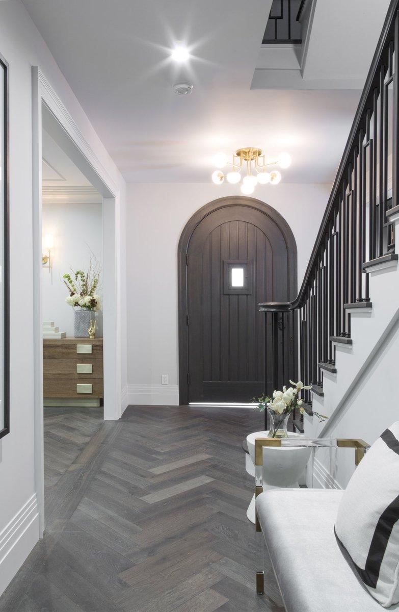 Arched door, herringbone flooring, and stunning staircase in entry of Drew's Honeymoon House