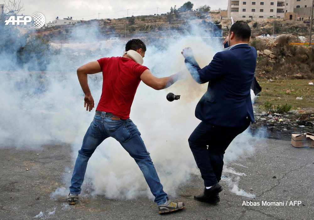 Palestinian protesters react to a stun grenade thrown by Israeli security forces during clashes in #Ramallah on December 13, 2017, over US President Donald Trump's recognition of Jerusalem as Israel's capital 📷 @Abbasmomani