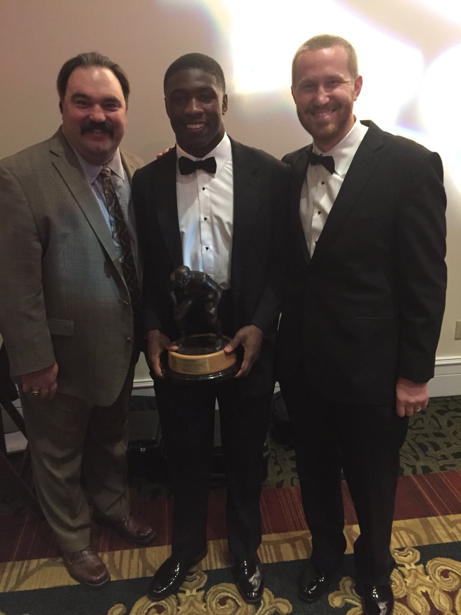 Georgia linebacker's coach Glenn Schumann (right) poses with Bulldog junior ILB Roquan Smith (middle) after being named and presented the 2017 Butkus  Award at the annual UGA football Gala in Athens. (Photo from Glenn Schumann / Twitter)