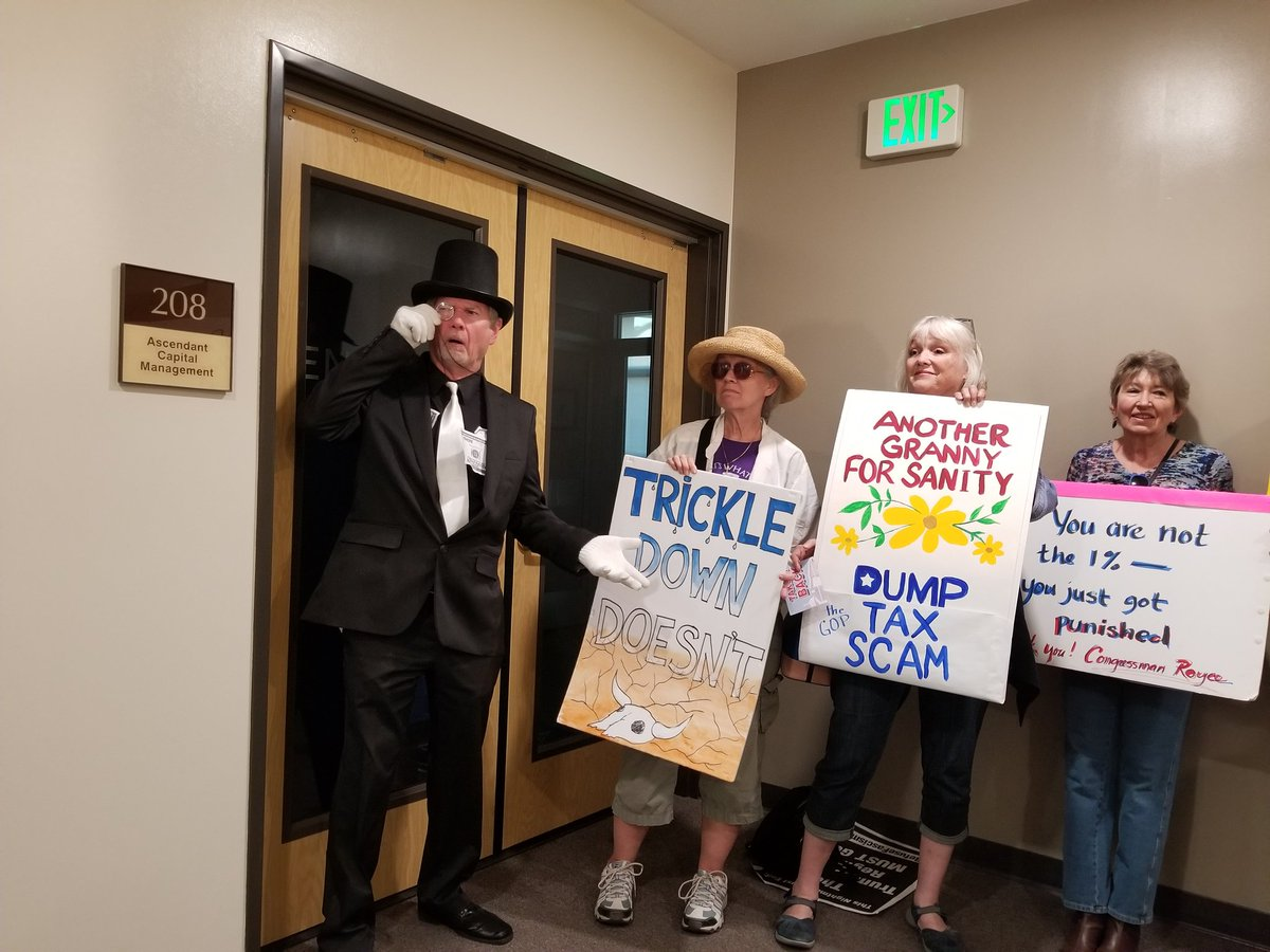 Protesters pose for photos in the hall outside Rep. Ed Royce's district office in Brea. (Christine Mai-Duc / Los Angeles Times)