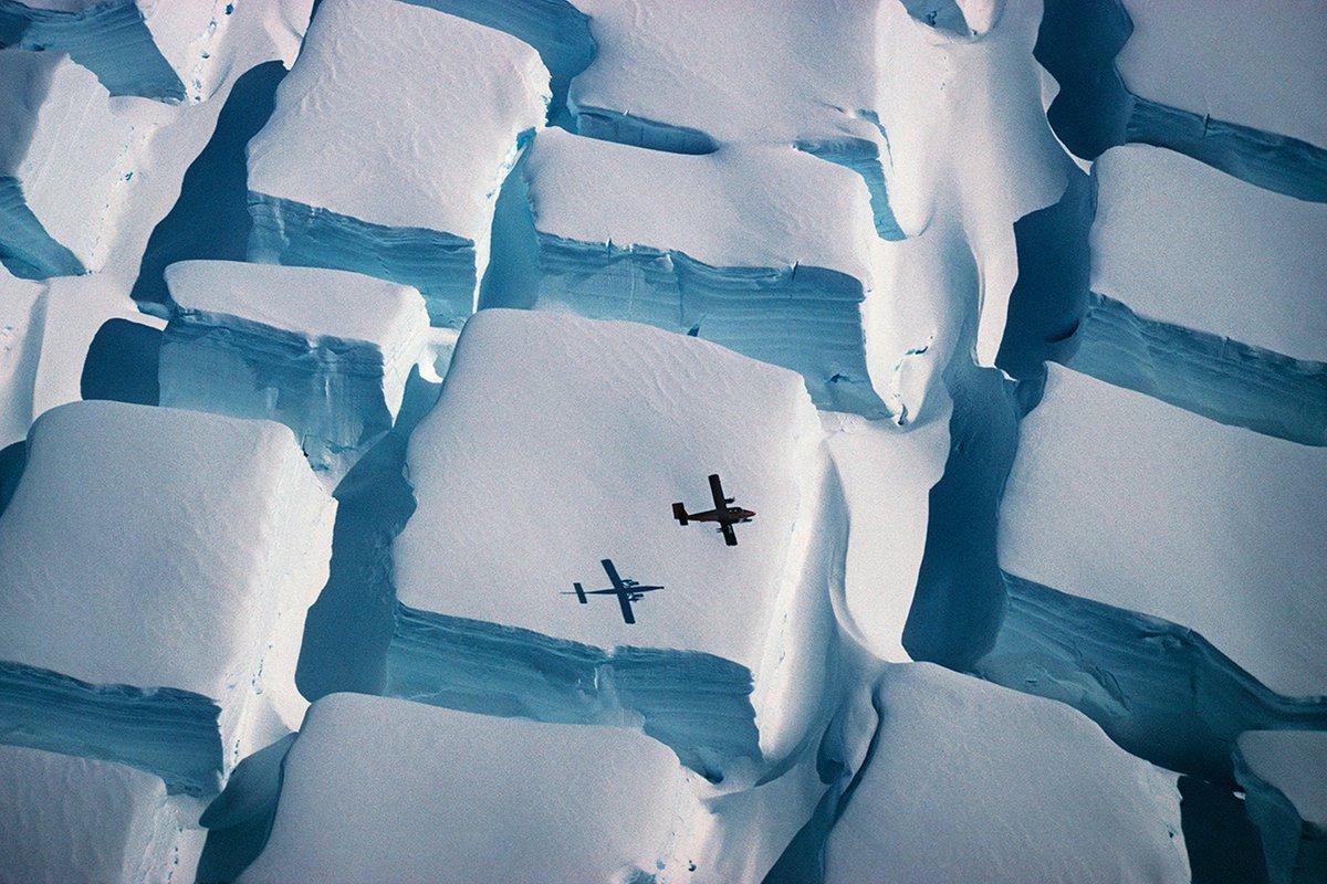南極大陸の氷床上空を飛ぶ飛行機