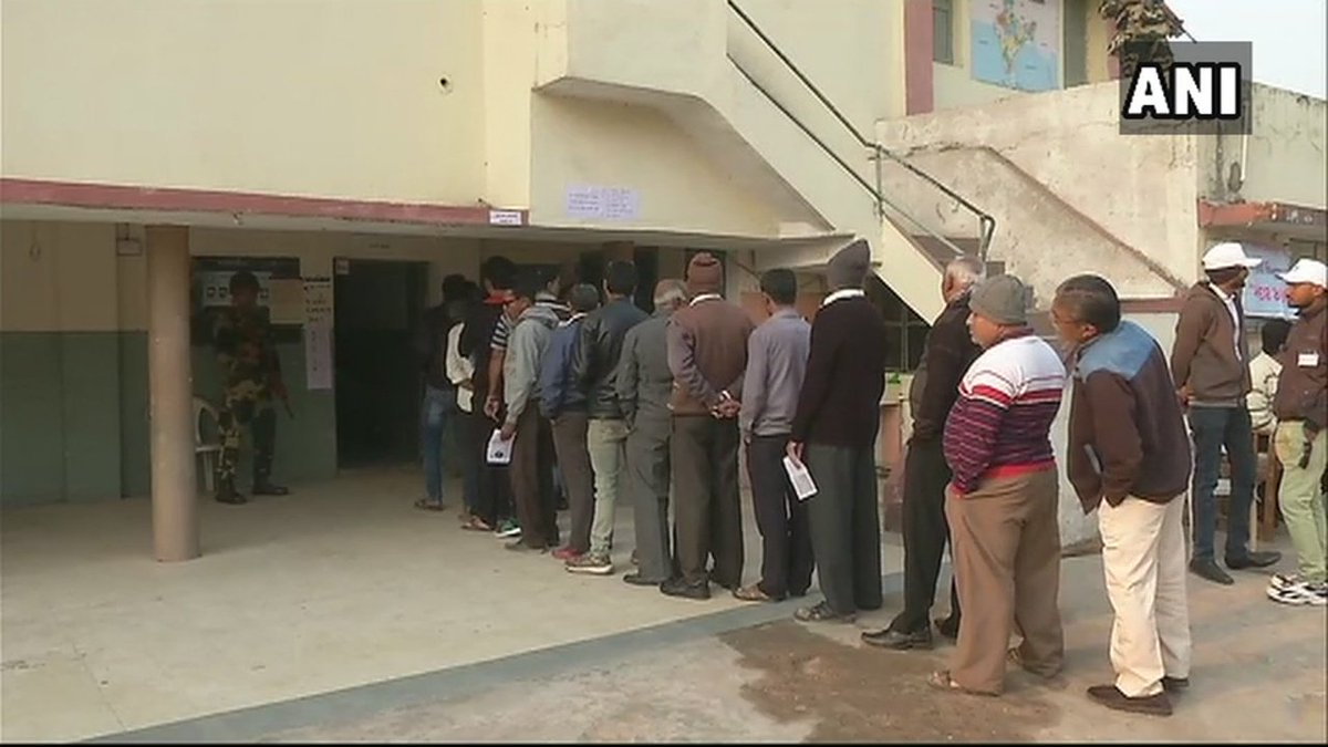 People queue up outside a polling statio...
