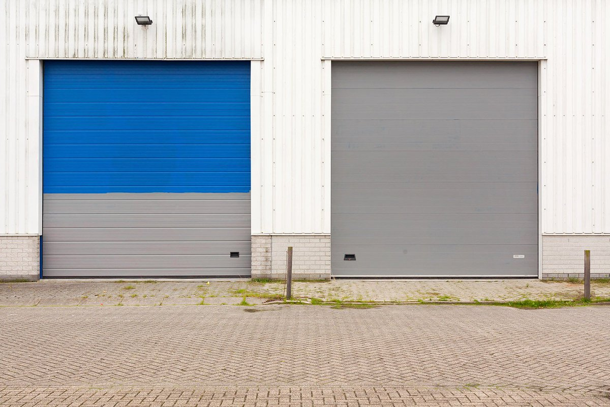 Vlokken van oude blauwe verf op grijze concrete muur stock foto