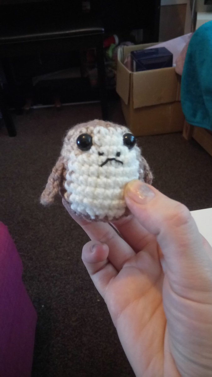 Crocheted porg held in my hand, a bit lumpy but otherwise looking as annoyed as the porg did at chewy