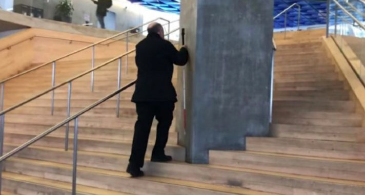 a blind man collides with a large pillar that interrupts a handrail going up the middle of a large staircase