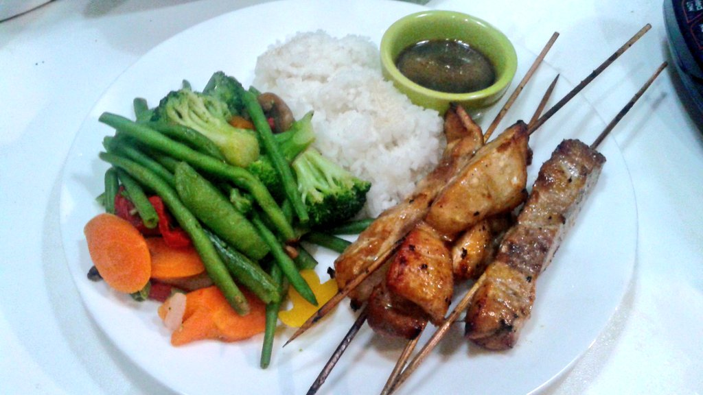 yakitori,  rice, and veggies on a white plate with a bowl of sauce